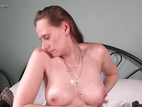 Long haired woman is trying to lick her tits while moving cunt on dildo