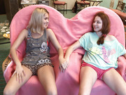Two young and kinky lesbians are playing with huge dildo indoors