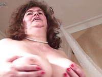 Curly horny woman is closing her boobs with hands and masturbating